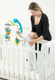 Jonge lachende moeder die met haar babyjongen bij het bed staat