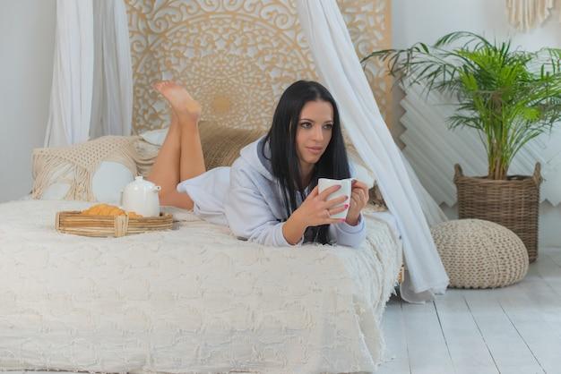 Jonge lachende mooie vrouw in wit overhemd wakker in de ochtend zittend op bed mooie vrouw met croissants en kopje koffie drinken in slaapkamer concept van voedsel levensstijl