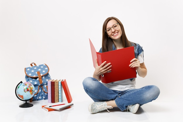 Jonge lachende mooie vrouw student in glazen met rode map voor papieren document zitten in de buurt van globe rugzak, schoolboeken geïsoleerd