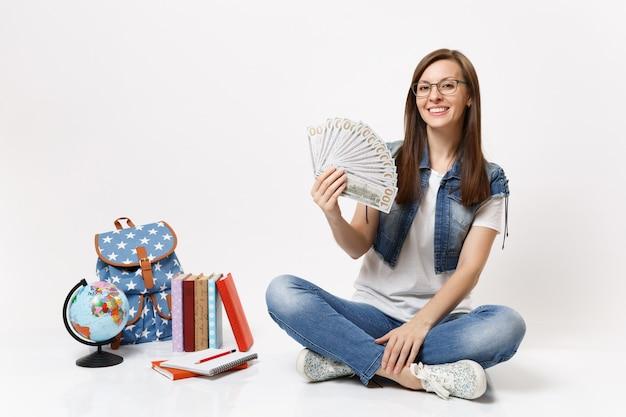 Jonge lachende mooie vrouw student met bundel veel dollars, contant geld zittend in de buurt van globe, rugzak, schoolboeken geïsoleerd