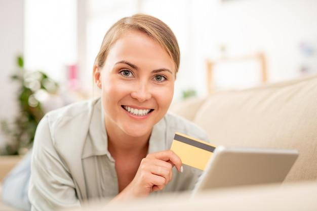 Jonge lachende online shopper met plastic kaart en touchpad bestellen terwijl liggend op de bank