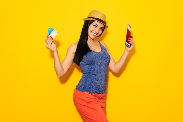 Jonge lachende opgewonden studente met paspoort instapkaart ticket en creditcard
