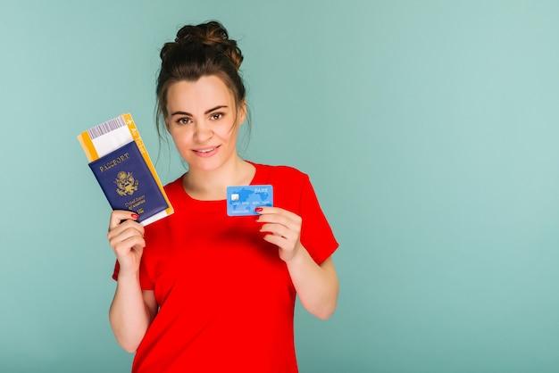 Jonge lachende opgewonden vrouw student met paspoort instapkaart ticket en creditcard geïsoleerd op blauwe achtergrond. vliegreizen vlucht - afbeelding