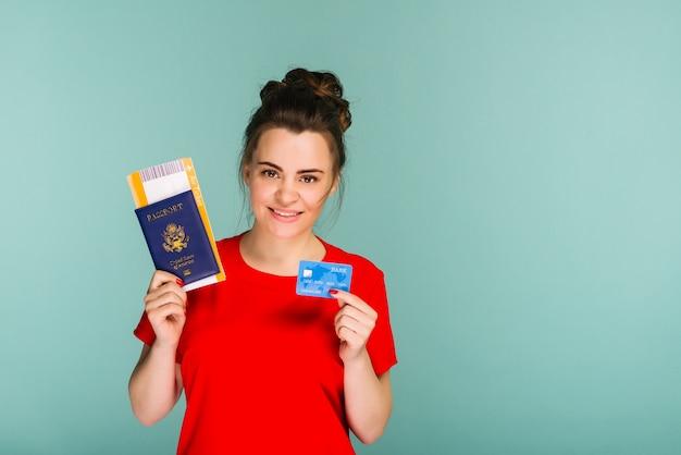 Jonge lachende opgewonden vrouw student met paspoort instapkaart ticket en creditcard geïsoleerd op blauwe achtergrond