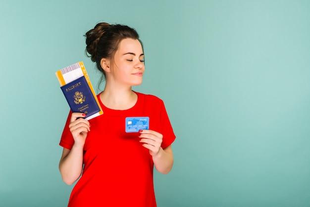 Jonge lachende opgewonden vrouw student met paspoort instapkaart ticket en creditcard geïsoleerd op blauwe ruimte. vliegreizen vlucht