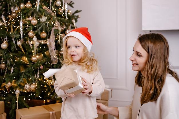 Jonge lachende ouders geven grappig dochtertje aanwezig op kerstmis, lachend meisje in kerstmuts met doos in handen. vakantie met het gezin. vakantie, cadeautjes, kerstmis, x-mas concept
