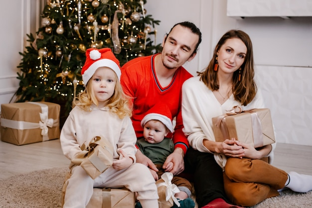 Jonge lachende ouders givingkids presenteert op kerstmis, schattig meisje in kerstmuts met doos in handen.