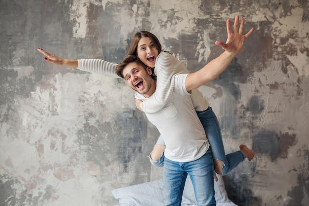 Jonge lachende paar spelen op bed thuis in casual outfit, man en vrouw samen plezier hebben, gekke positieve emotie, gelukkig, hand omhoog houden