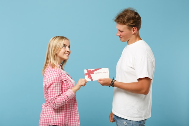 Jonge lachende paar twee vrienden, man en vrouw in wit roze lege lege t-shirts poseren