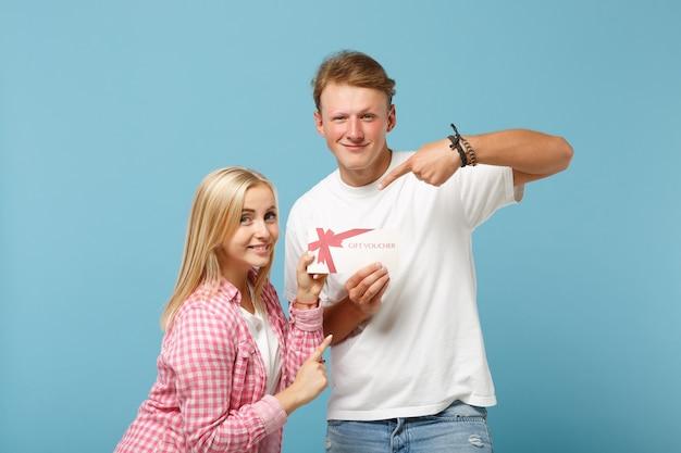Jonge lachende paar twee vrienden, man en vrouw in wit roze lege t-shirts poseren