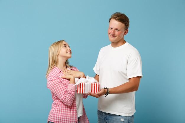 Jonge lachende paar twee vrienden man en vrouw in wit roze t-shirts poseren