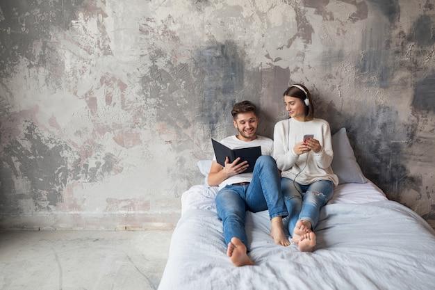 Jonge lachende paar zittend op bed thuis in casual outfit leesboek dragen jeans, man leesboek, vrouw luisteren naar muziek op koptelefoon, romantische tijd samen doorbrengen