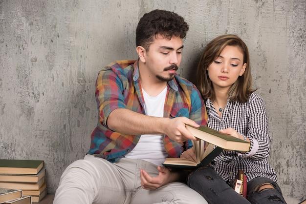 Jonge lachende paar zittend op de vloer met boeken