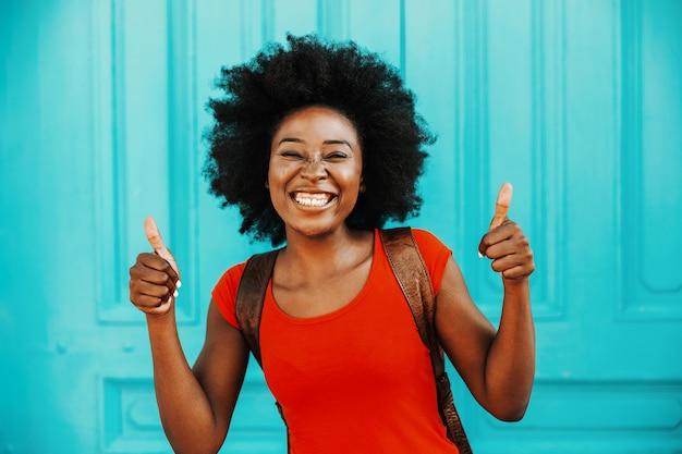 Jonge lachende prachtige afrikaanse vrouw met kort krullend haar permanent buiten en duimen opdagen. diversiteit concept.