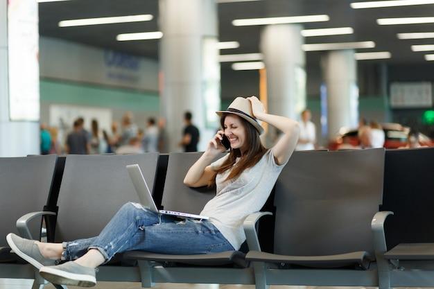 Jonge lachende reiziger toeristische vrouw die op laptop werkt, praat op mobiele telefoon, belt vriend op luchthaven