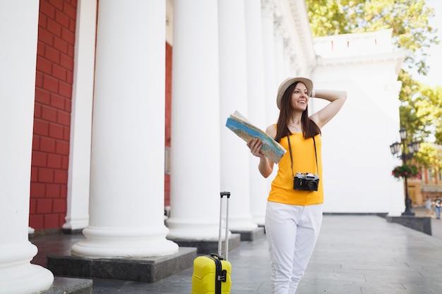Jonge lachende reiziger toeristische vrouw in gele kleding met koffer stadskaart retro vintage fotocamera in de stad buiten. meisje dat naar het buitenland reist om een weekendje weg te reizen. toeristische reis levensstijl.