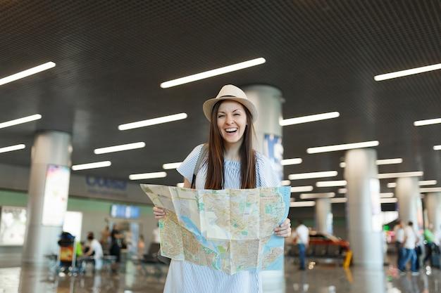 Jonge lachende reiziger toeristische vrouw in hoed met papieren kaart, route zoeken en wachten in lobby hal op internationale luchthaven