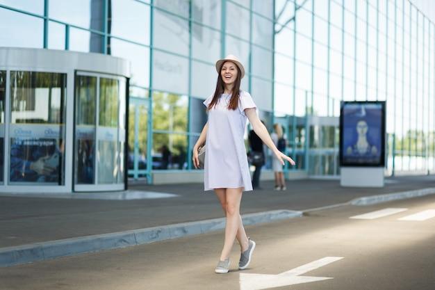 Jonge lachende reiziger toeristische vrouw in hoed met rugzak staande op de internationale luchthaven