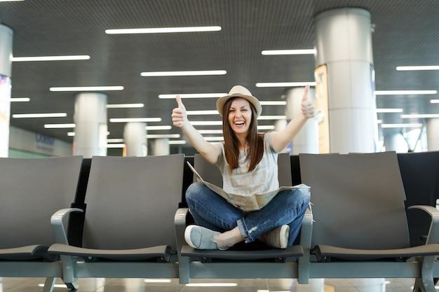 Jonge lachende reiziger toeristische vrouw met papieren kaart zittend met gekruiste benen, duimen opdagen, wachten in de lobby hal op de luchthaven