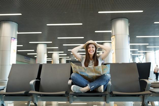 Jonge lachende reizigerstoerist met papieren kaart zittend met gekruiste benen, zich vastklampend aan het hoofd, wachtend in de lobby op de luchthaven