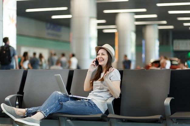 Jonge lachende reizigerstoeristenvrouw die aan laptop werkt, praat op mobiele telefoon, belt vriend, boekt taxihotel wacht in lobbyhal op luchthaven