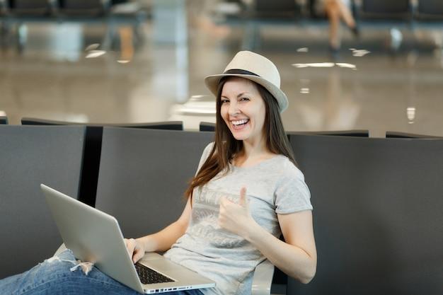 Jonge lachende reizigerstoeristenvrouw die op laptop werkt, duim opsteekt en wacht in de lobbyhal op de internationale luchthaven
