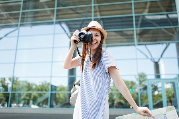 Jonge lachende reizigerstoeristenvrouw maakt foto's op retro vintage fotocamera met papieren kaart op internationale luchthaven
