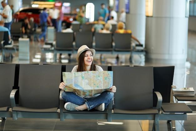 Jonge lachende reizigerstoeristenvrouw met gekruiste benen houdt een papieren kaart vast en kijkt opzij in de lobbyhal op de internationale luchthaven