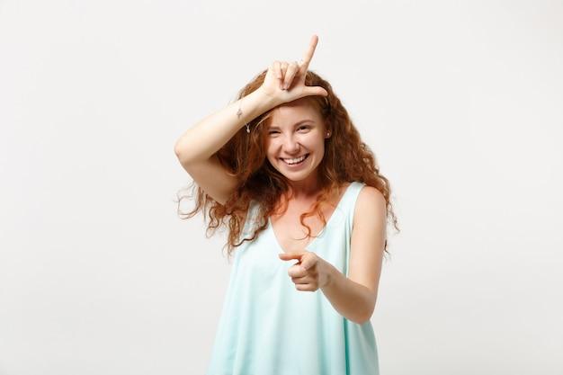 Jonge lachende roodharige vrouw in casual lichte kleding poseren geïsoleerd op een witte muur achtergrond. mensen levensstijl concept. bespotten kopie ruimte. verliezersgebaar tonen, wijsvinger op camera richten.