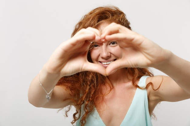 Jonge lachende roodharige vrouw meisje in casual lichte kleding poseren geïsoleerd op een witte achtergrond in de studio. mensen levensstijl concept. bespotten kopie ruimte. vormhart met handen, hartvormig teken tonen.
