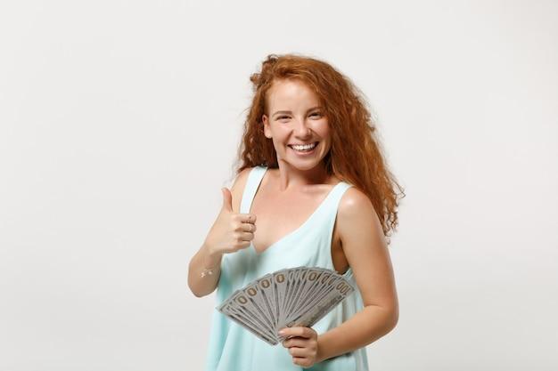 Jonge lachende roodharige vrouw meisje in casual lichte kleding poseren geïsoleerd op een witte achtergrond. mensen levensstijl concept. bespotten kopie ruimte. houd fan van contant geld in dollarbankbiljetten met duim omhoog.