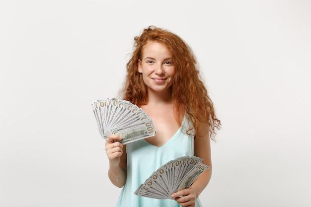 Jonge lachende roodharige vrouw meisje in casual lichte kleding poseren geïsoleerd op een witte achtergrond, studio portret. mensen levensstijl concept. bespotten kopie ruimte. houd fan van contant geld in dollarbankbiljetten.