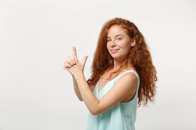 Jonge lachende roodharige vrouw meisje in casual lichte kleding poseren geïsoleerd op een witte achtergrond, studio portret. mensen oprechte emoties levensstijl concept. bespotten kopie ruimte. hand in hand als een pistool.