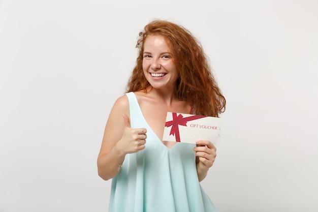 Jonge lachende roodharige vrouw meisje in casual lichte kleding poseren geïsoleerd op een witte muur achtergrond studio portret. mensen levensstijl concept. bespotten kopie ruimte. met duim omhoog houden cadeaubon.