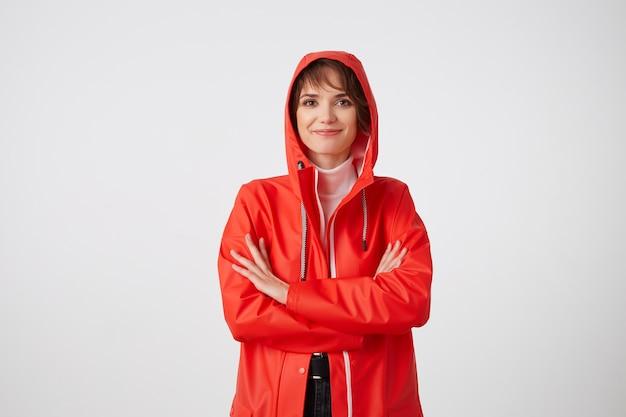 Jonge lachende schattige kortharige vrouw gekleed in rode regenjas, op zoek met een gelukkige uitdrukking, staande met gekruiste armen. positieve emotie concept.