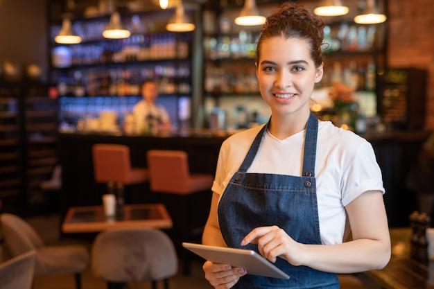 Jonge lachende serveerster in schort en t-shirt staan voor camera tijdens het gebruik van touchpad en het ontmoeten van gasten in café