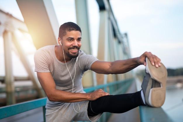 Jonge lachende sportman hardlopen voorbereiden