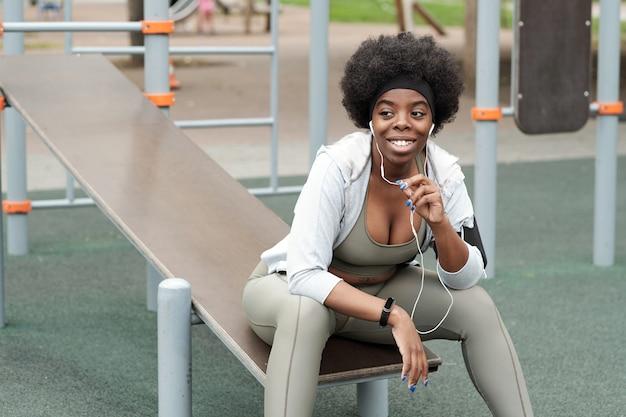 Jonge lachende sportvrouw met koptelefoon communiceren via mobiele technologieën