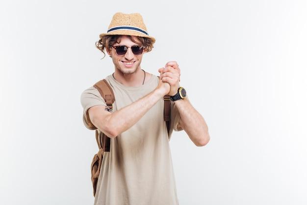 Jonge lachende stijlvolle man goed gedaan gebaar tonen op witte achtergrond