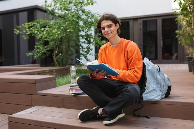 Jonge lachende student zit met boek in handen en gelukkig op de binnenplaats van de universiteit