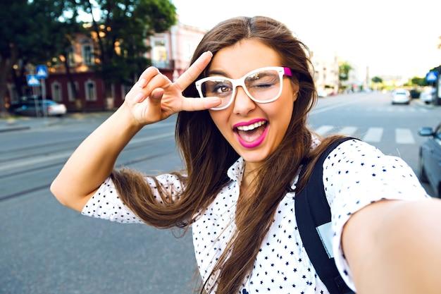 Jonge lachende tiener gelukkige vrouw selfie maken op straat, leng haren, lichte make-up en schattige heldere bril, alleen reizen, plezier, positieve stemming, vreugde, vakantie