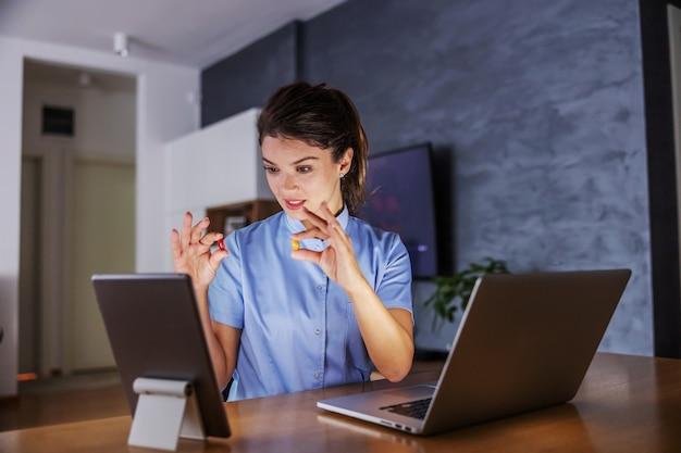 Jonge lachende vriendelijke verpleegster om thuis te zitten en pillen te houden tijdens het geven van adviezen via internet.