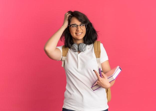 Jonge lachende vrij kaukasische schoolmeisje met koptelefoon op nek dragen van bril en terug tas legt hand op haar bedrijf boek kijkt kant op roze met kopie ruimte
