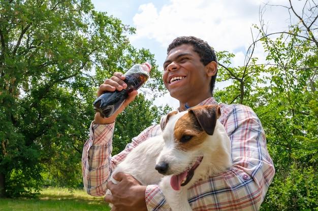 Jonge lachende vrolijke afro-amerikaanse man die jack russell terrier-hond vasthoudt en cola drinkt uit een fles buitenshuis. wandelen in het park in de zomer, lage kijkhoek