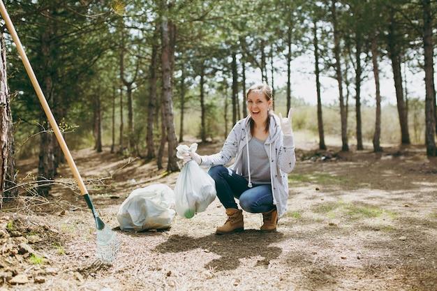 Jonge lachende vrouw die afval schoonmaakt met vuilniszakken met een rock-n-roll-bord in het park