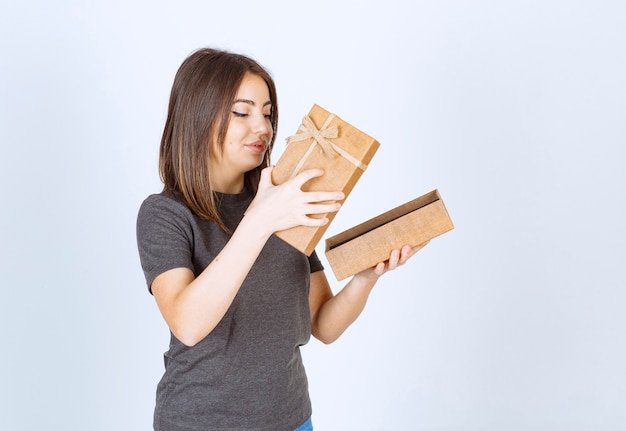 Jonge lachende vrouw die een geschenkdoos opent.