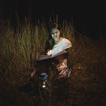 Jonge lachende vrouw die een magisch boek leest 's nachts bos