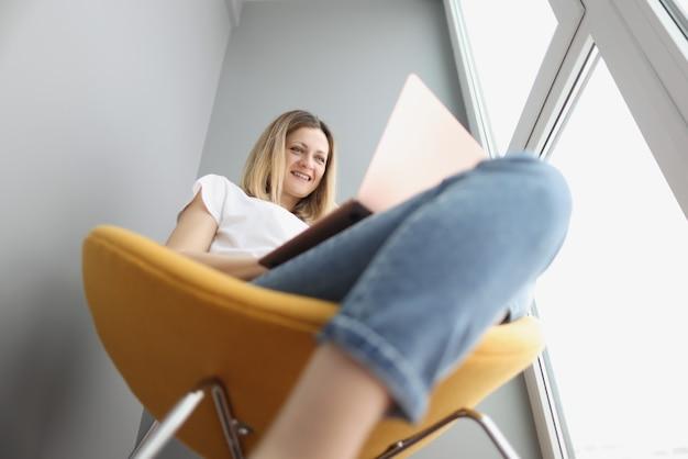 Jonge lachende vrouw die in een gele fauteuil zit en naar het scherm van de laptop kijkt