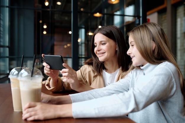 Jonge lachende vrouw en haar schattige dochter zitten in café