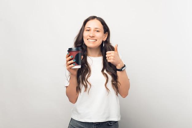 Jonge lachende vrouw geeft een like aan de koffie die ze net heeft gedronken.